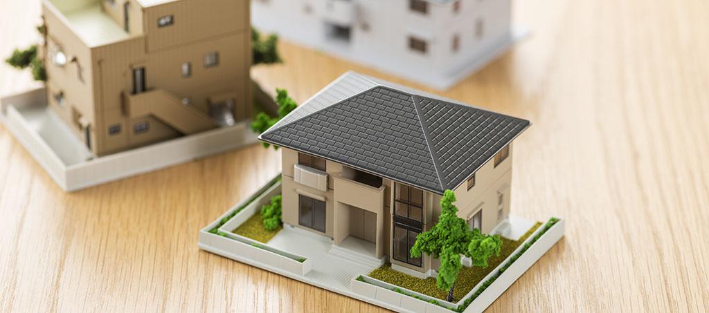 Schreibtischoberfläche mit kleinem Modellhaus und Unterlagen zu Bodenrichtwerten