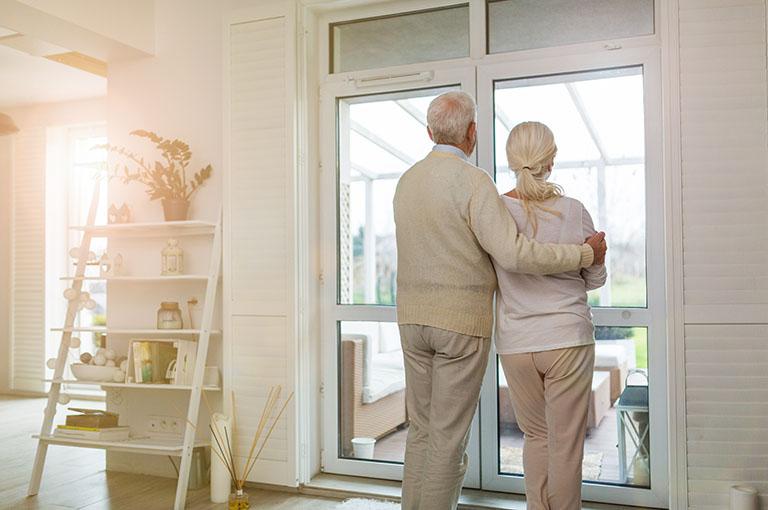 Altes Ehepaar steht umarmend vor einem Haus