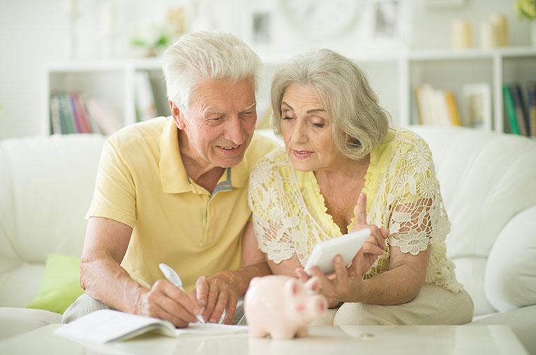 Altes Ehepaar berechnet Geld in Sparschwein