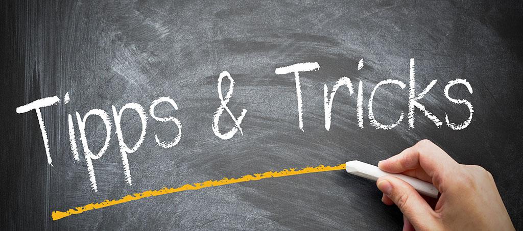 """Mann scheibt """"Tipps & Tricks"""" auf Tafel"""