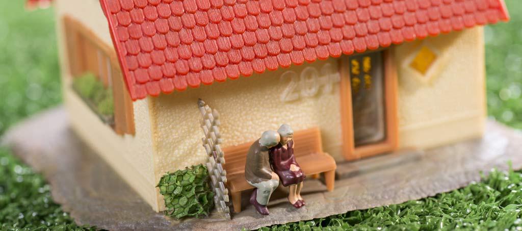 Modellhaus mit älterem Paar als Symbolbild für Immobilie als Altersvorsorge in München